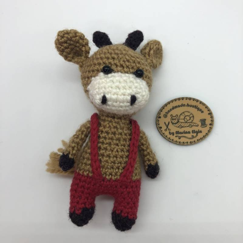 Brown cow with red trousers with braces