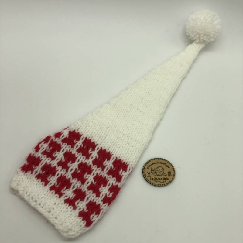 White hat with red pattern and white pompon